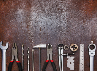 Metal workshop tools on old metal background