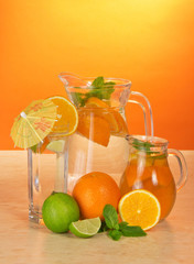 Jugs with drink, glass and a citrus