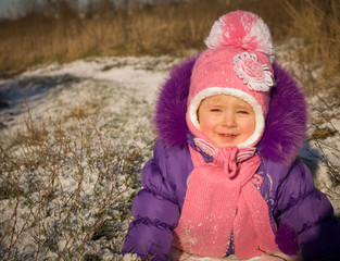 Portrait of happy little girl in snowy landscape
