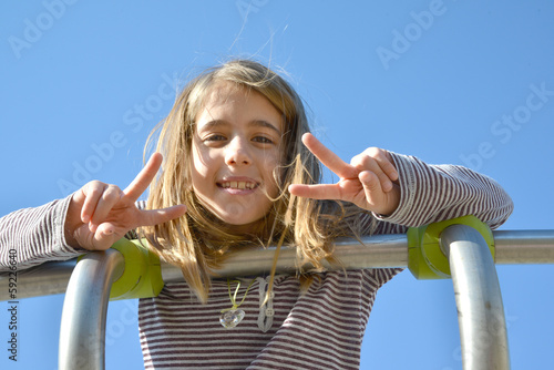 Blond girl making victory sign with her hand