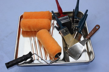 A decorators paint tray with rollers and brushes