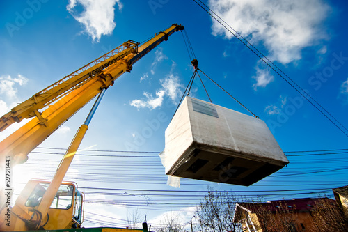 Industrial Crane operating and lifting an electric generator - 59228443