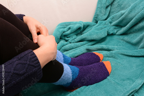 Woman hugging her legs, wearing warm socks