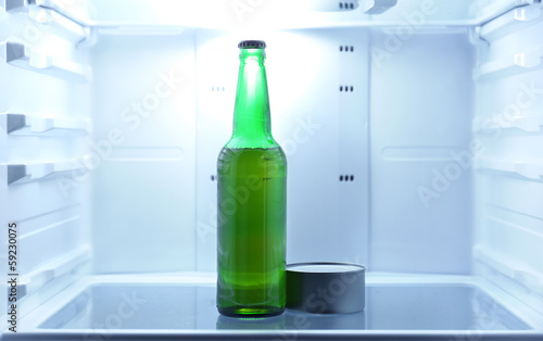 One  beer bottle and canned tune in open empty refrigerator:
