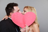 happy bride and groom kissing behind red heart