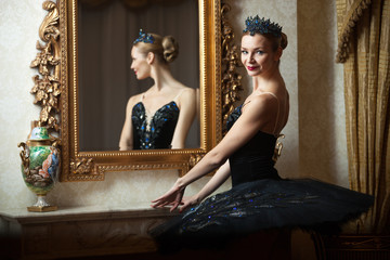 Ballerina in black tutu standing in front of mirror