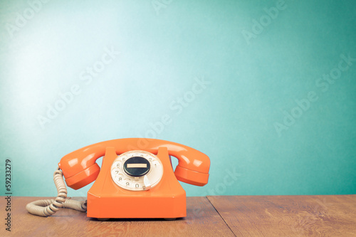 Retro orange telephone on wood table near aquamarine background