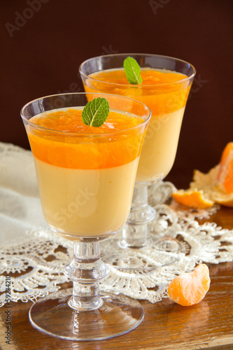 orange panna cotta with slices of oranges.