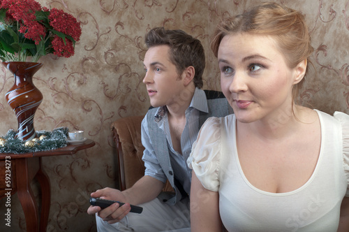 a pair of young beautiful people watching television Poster