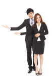 Young smiling business woman and man with welcome gesture