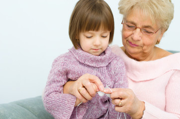 grandmother with granddaughter knitting