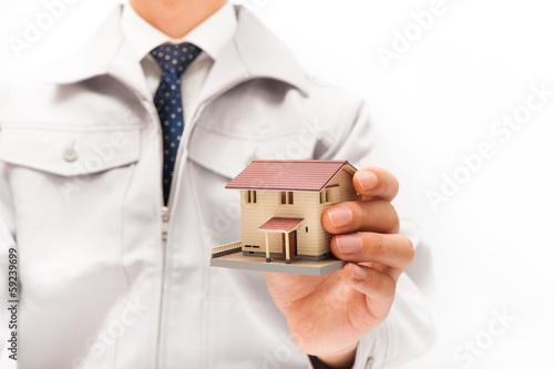 作業着を着て住宅販売を行う男性