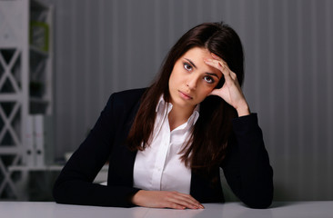 Young pensive businesswoman sitting at the table