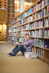 Cheerful student sitting on library floor reading
