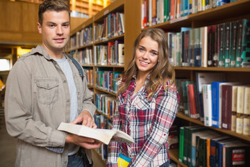 Happy classmates standing in library looking at camera