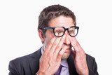 Close-up of a worried businessman rubbing eyes