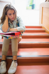 Troubled student sitting on stairs