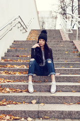 Teen girl sitting on stairs against grunge wall