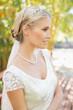 Pretty smiling blonde bride standing on a bridge