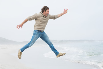 Side view of a casual man jumping at beach