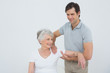 Physiotherapist massaging a smiling senior woman's arm