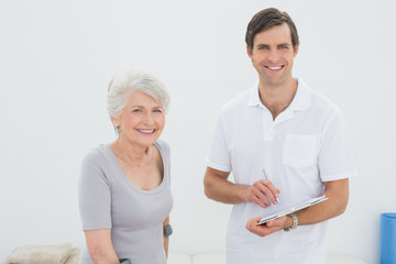 Smiling male therapist and disabled senior patient