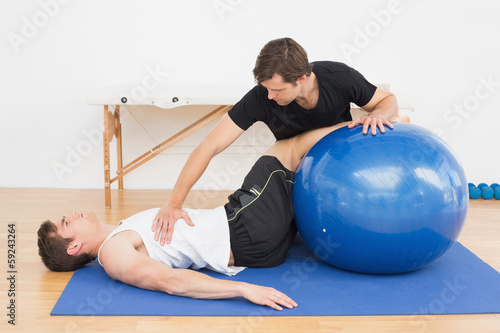Physical therapist assisting young man with yoga ball