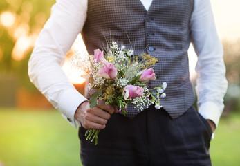 Groom holding wedding bouquet