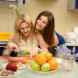 Happy daughter teenager with her mother peel and cut vegetables