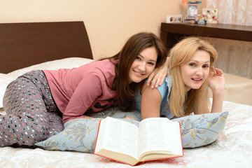 young daughter with mother reading book and resting in bed at ho
