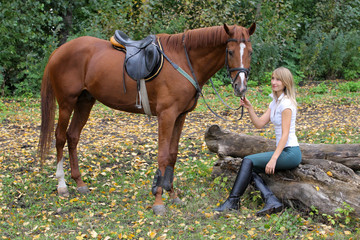 Elegant woman posing with brown racehorse