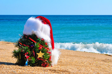 Christmas tree and santa hat on the sand in the beach