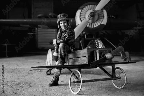 Leinwanddruck Bild Young Aviator in aircraft in a hangar