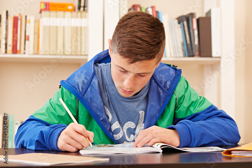 Male teenager concentrated doing homework