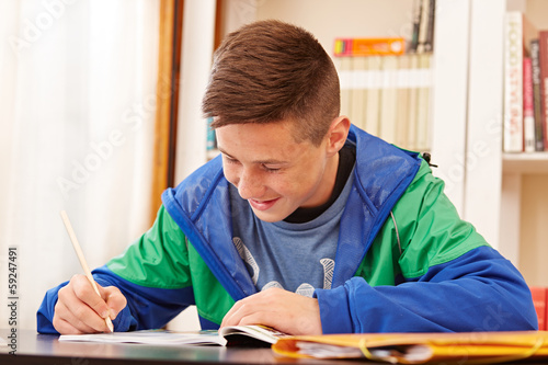 Male confident teenager doing homework