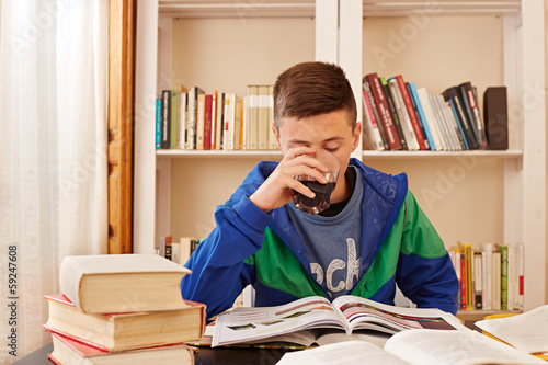 Male teenager drinking coke while studying