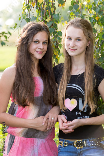 two teenage girls near birch