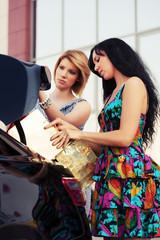 Young women loading shopping bags in a car trunk