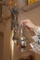 hand of catholic priest at incense of cross