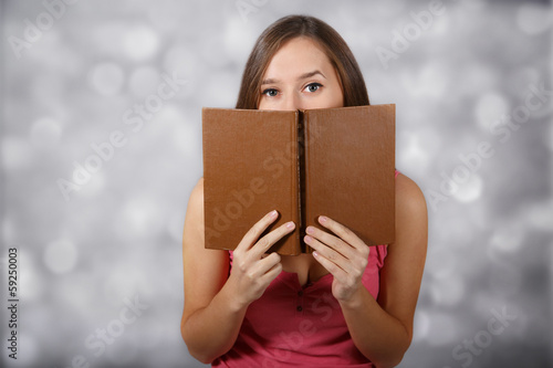 Girl covers her face with book at light background