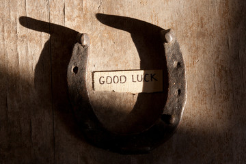 good luck inscription and  horseshoe over wooden background
