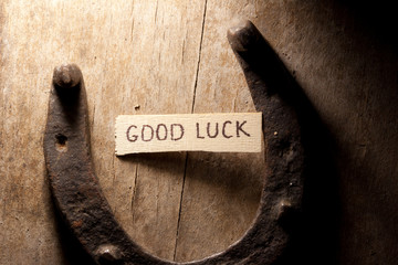 good luck tag and  horseshoe over wooden background