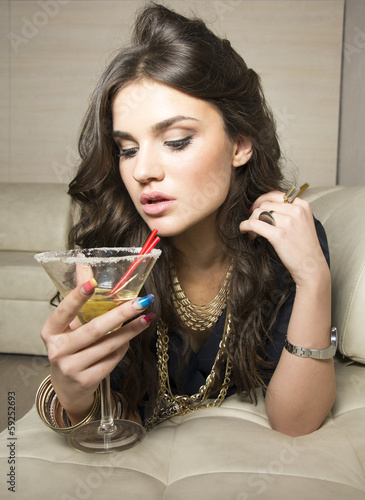 Beautiful woman laying on sofa and holding a glass of martini