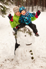 Little boy and mother posing on big snowman in winter
