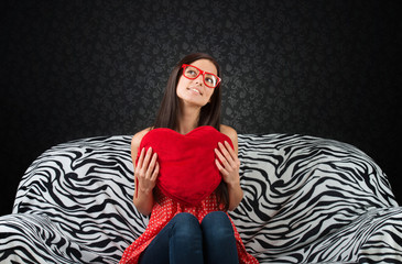 Girl with heart cushion sitting on the sofa and looking up