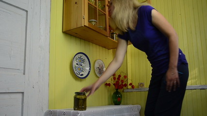 girl takes from cupboard four jars with pickles vegetable