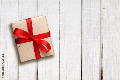 Gift box with red bow on white wooden background