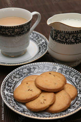 Plate full of biscuits served with milk pot and a cup of tea