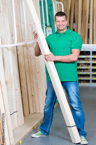 lächelnder mann kauft holzlatten im fachmarkt