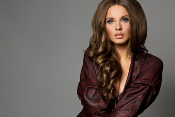 Pretty attractive erotic brunette woman in maroon jacket, grey b